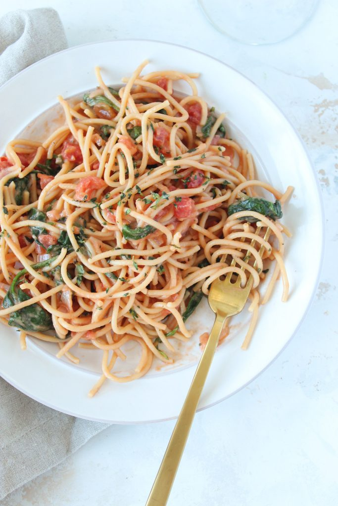 Fresh Tomato Pasta on a white plate with golden spoon